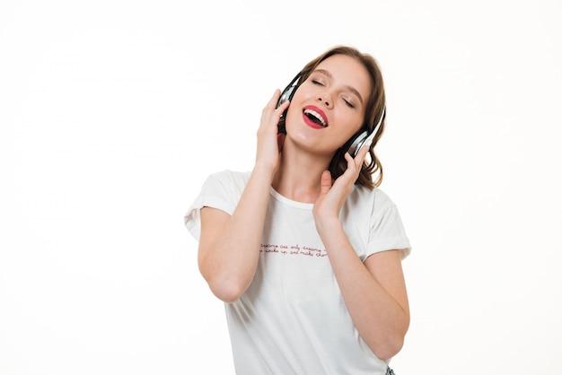 Portret van een gelukkig meisje dat aan muziek met hoofdtelefoons luistert