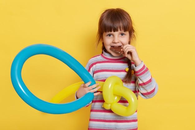 Portret van een gelukkig meisje dat chocolade eet en balloncijfer houdt, camera met tevreden uitdrukking bekijkt die over gele muur wordt geïsoleerd.