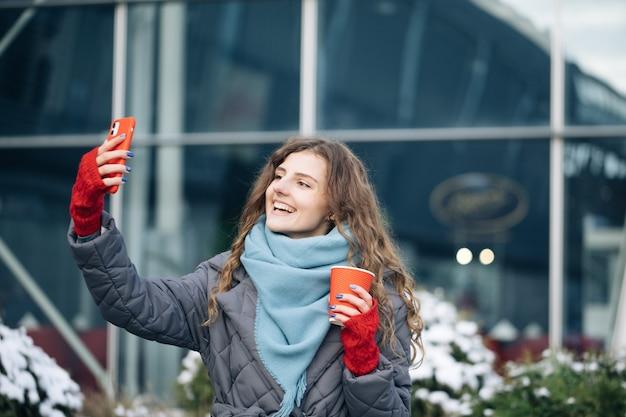 Portret van een gelukkig meisje dat de camera van de selfieholding neemt bij stadsstraat.