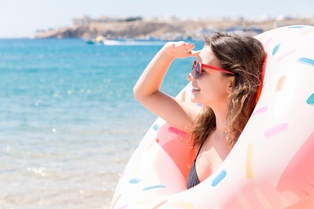 Portret van een gelukkig meisje dat door een opblaasbaar ringverblijf op het zeestrand kijkt. zomervakantie en vakantie concept.