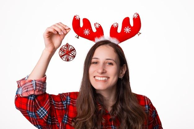 Portret van een gelukkig meisje dat het kostuum van kerstmisherten draagt terwijl status en een kleine vlokbol vasthoudt