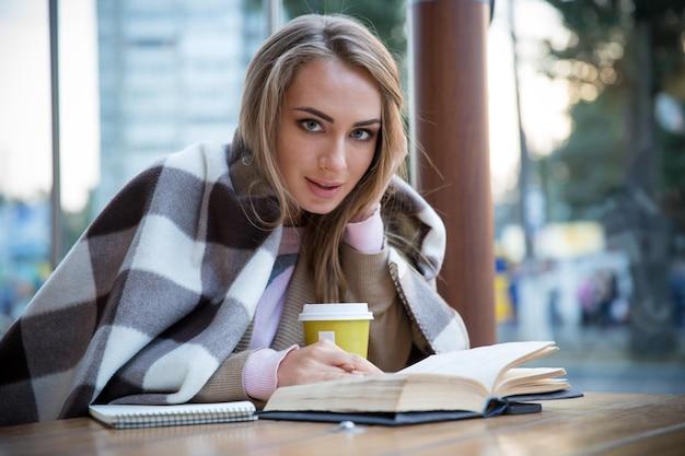 Portret van een gelukkig meisje dat met boek in café zit