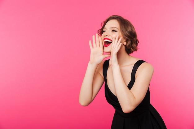 Portret van een gelukkig meisje gekleed in zwarte jurk schreeuwen