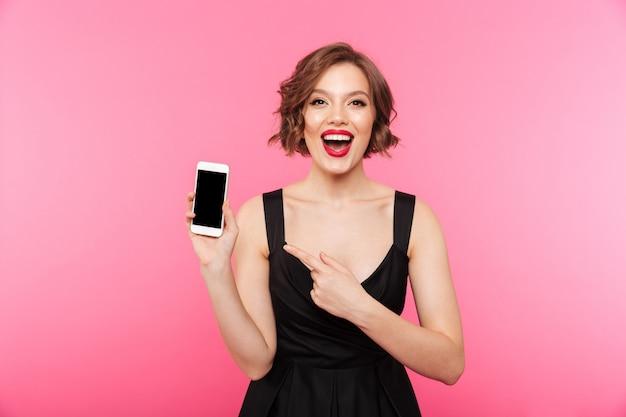 Portret van een gelukkig meisje gekleed in zwarte jurk wijzend