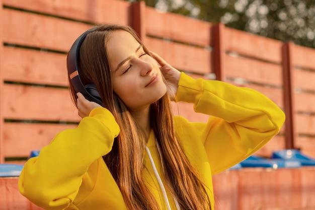 Portret van een gelukkig meisje in draadloze hoofdtelefoons in de zomer op een stadsstraat op een zonnige dag