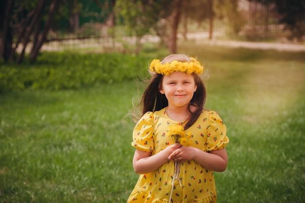 Portret van een gelukkig meisje in een gele zomerjurk en haar dat in de wind waait met een krans van gele d...