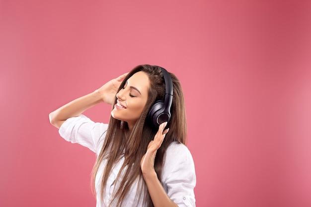 Portret van een gelukkig meisje luisteren muziek met draadloze koptelefoon van een smartphone