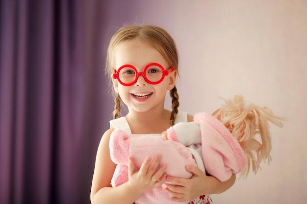 Portret van een gelukkig meisje met een pop in haar armen