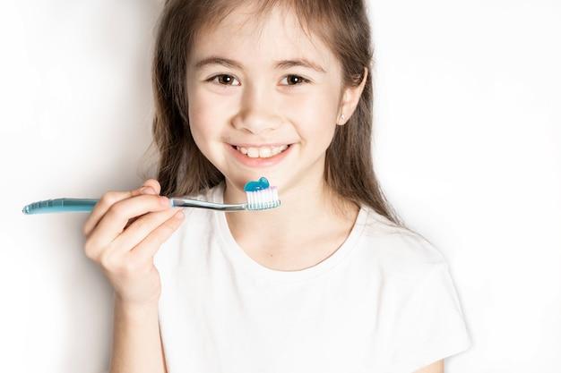 Portret van een gelukkig meisje met een tandenborstel, glimlachen en kijken, klaar om zijn tanden te poetsen. tanden verzorgen