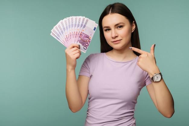 Portret van een gelukkig meisje wijzende vinger op stelletje geld bankbiljetten geïsoleerd dan blauw