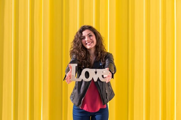 Portret van een gelukkig mooi jong de liefdewoord van de vrouwenholding over geel. vrijetijdskleding. plezier en levensstijl.