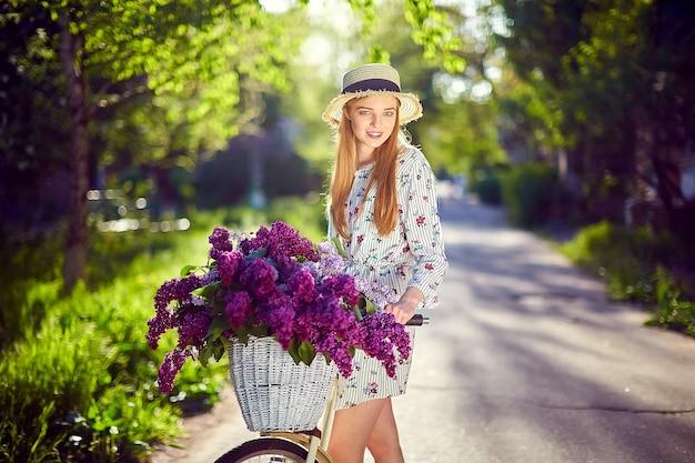 Portret van een gelukkig mooi jong meisje met vintage fiets en bloemen op de achtergrond van de stad in het zonlicht buiten. fiets met mand vol bloemen. actief vrijetijdsconcept.