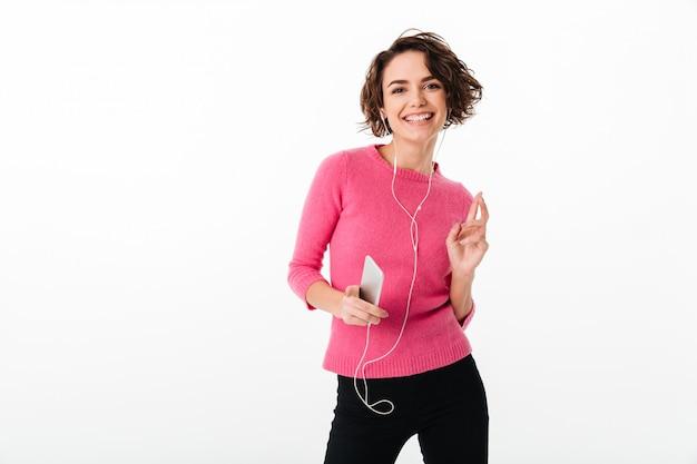 Portret van een gelukkig mooi meisje dat aan muziek luistert