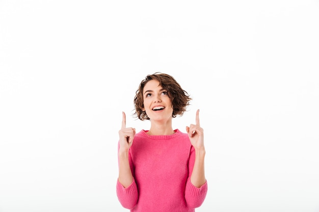 Portret van een gelukkig mooi meisje dat twee vingers richt