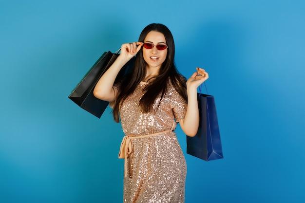 Portret van een gelukkig mooi meisje in elegante jurk en rode zonnebril boodschappentassen houden en kijken naar camera geïsoleerd op blauwe achtergrond.