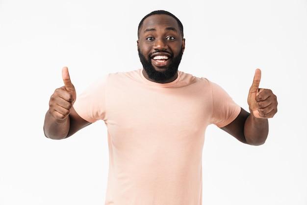 Portret van een gelukkig opgewonden afrikaanse man met een t-shirt dat geïsoleerd over een witte muur staat, duimen omhoog