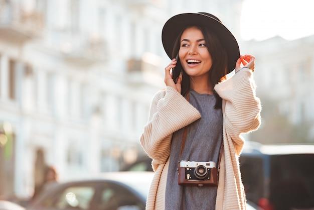 Portret van een gelukkig opgewonden vrouw praten op mobiele telefoon
