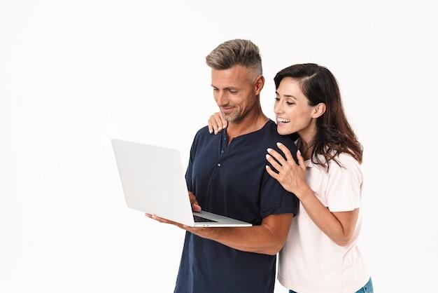 Portret van een gelukkig optimistisch vrolijk positief volwassen verliefde paar geïsoleerd over witte muur met behulp van laptopcomputer.