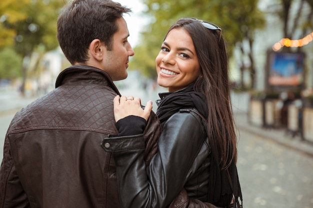 Portret van een gelukkig paar dat buiten loopt en terugkijkt op voorzijde