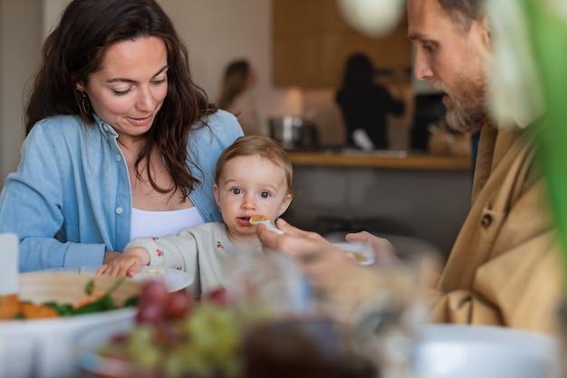 Portret van een gelukkig paar dat thuis lunch eet aan tafel, de baby voedt