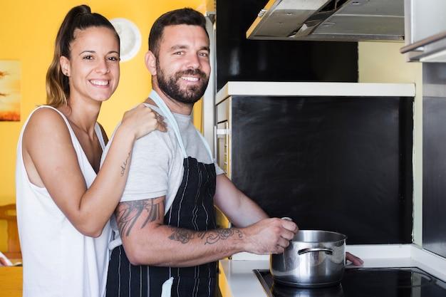 Portret van een gelukkig paar die voedsel in keuken voorbereiden