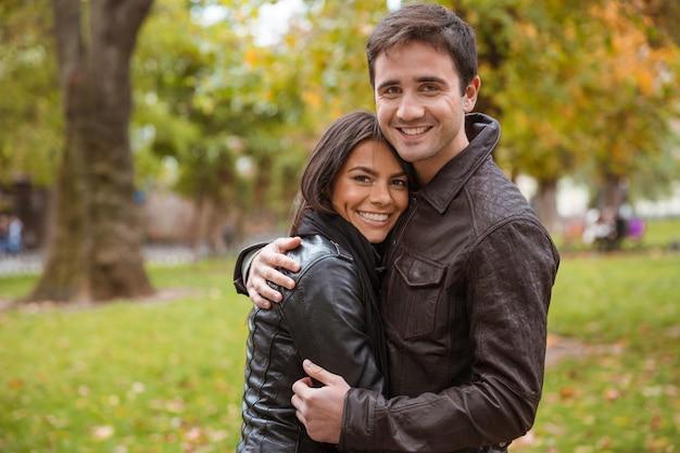 Portret van een gelukkig paar knuffelen buiten in het park en kijken naar de voorkant