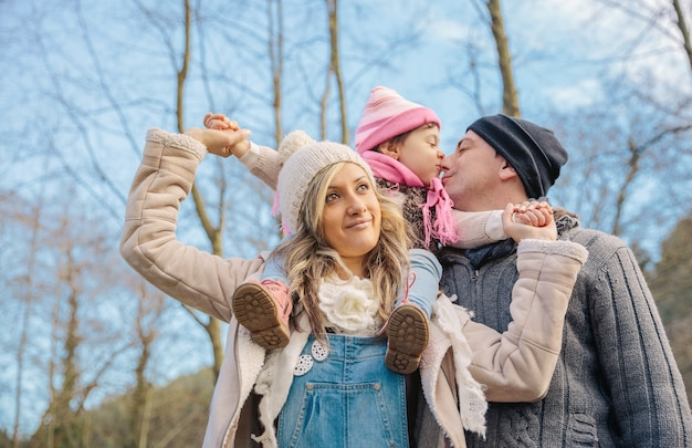 Portret van een gelukkig paar met haar dochtertje dat samen geniet van vrije tijd over een bosachtergrond. familie tijd concept.