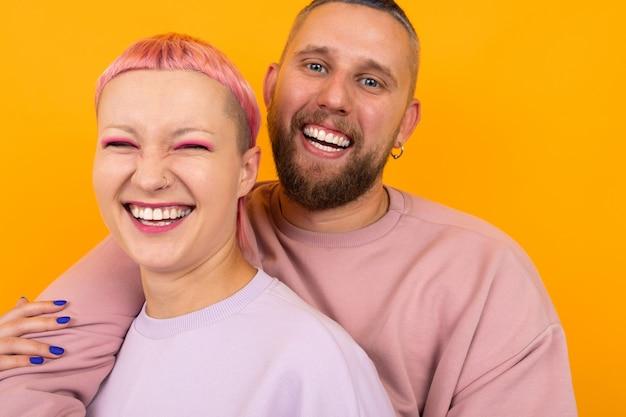 Portret van een gelukkig paar van man en vrouw met gekleurd haar en piercings gekleed in caasual roze kleren staan op geel