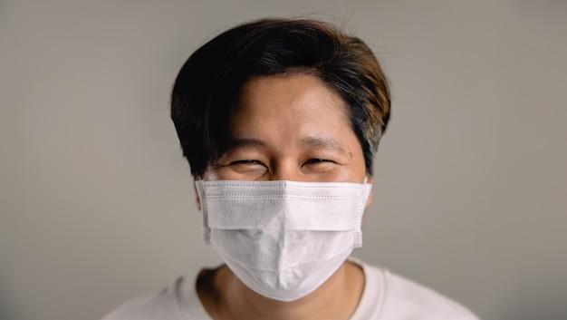 Portret van een gelukkig persoon, die een chirurgisch masker draagt, staande tegen de witte muur, glimlachend in een masker