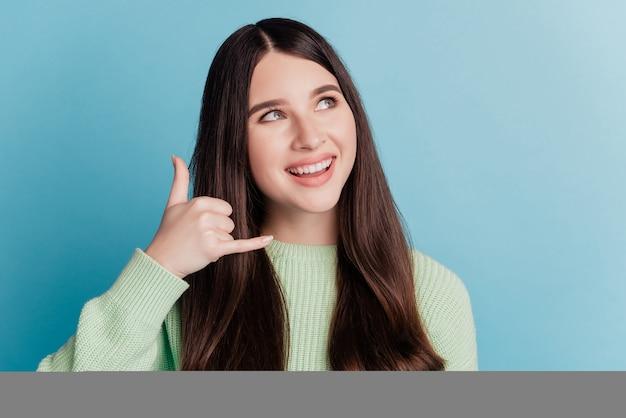 Portret van een gelukkig positief meisje laat me terugbellen, een gebaar dat er lege ruimte uitziet