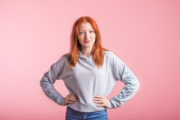 Portret van een gelukkig roodharig meisje in de studio op een roze achtergrond