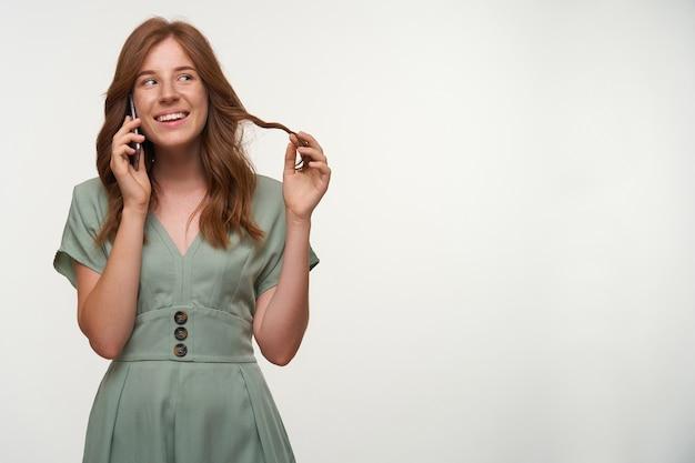 Portret van een gelukkig roodharige meisje in een romantische jurk opzij kijken en breed glimlachen, praten over de telefoon en haar op de vinger draaien, geïsoleerd