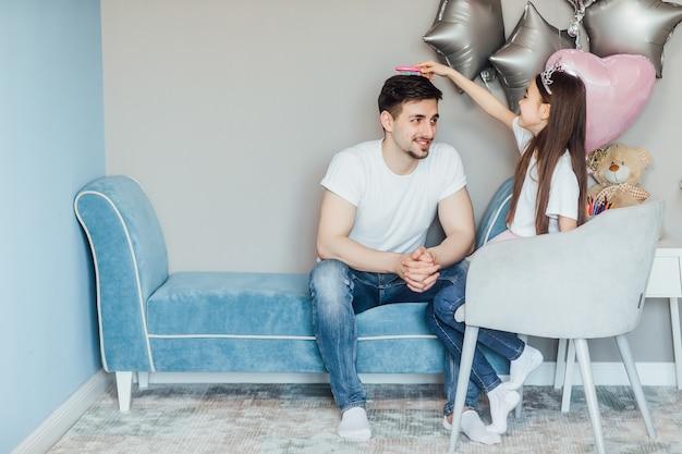 Portret van een gelukkig schattig klein kaukasisch dochtertje en haar knappe vader die samen in de slaapkamer spelen