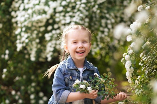 Portret van een gelukkig schattig meisje met witte bloemen
