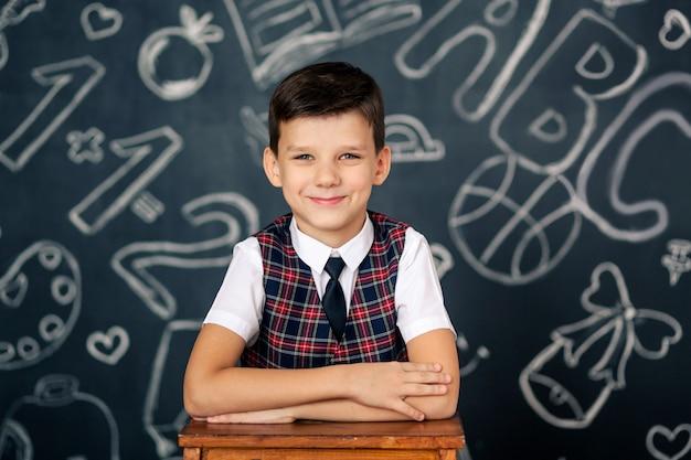Portret van een gelukkig schattige schooljongen op zwart bord ruimte