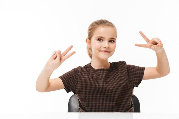Portret van een gelukkig schoolmeisje dat lacht en een vredesteken toont terwijl ze aan het bureau zit in de klas geïsoleerd over een witte muur