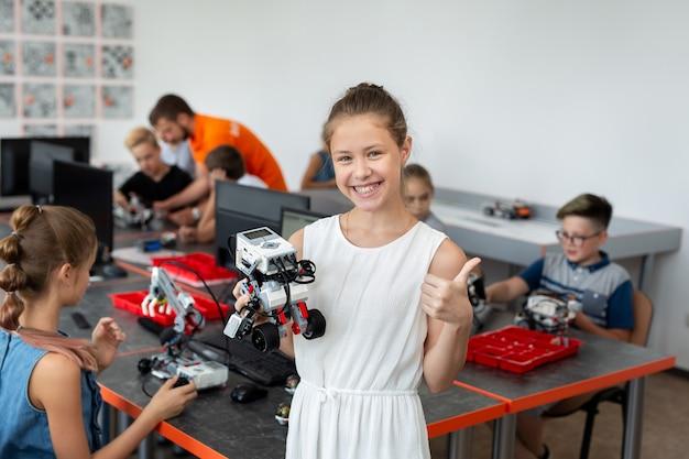 Portret van een gelukkig schoolmeisje in een robotica-klas, ze houdt een robot vast die is samengesteld uit plastic onderdelen die op een computer zijn geprogrammeerd