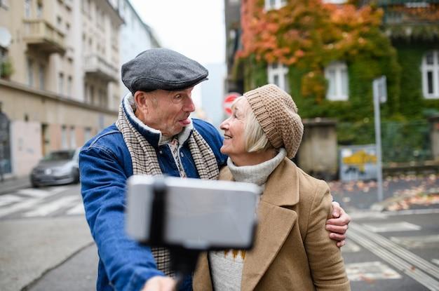 Portret van een gelukkig senior koppel dat buiten op straat in de stad loopt en selfie neemt.