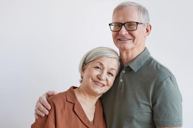 Portret van een gelukkig senior koppel dat de camera omhelst en naar de camera kijkt terwijl ze tegen een witte achtergrond staan, kopieer ruimte
