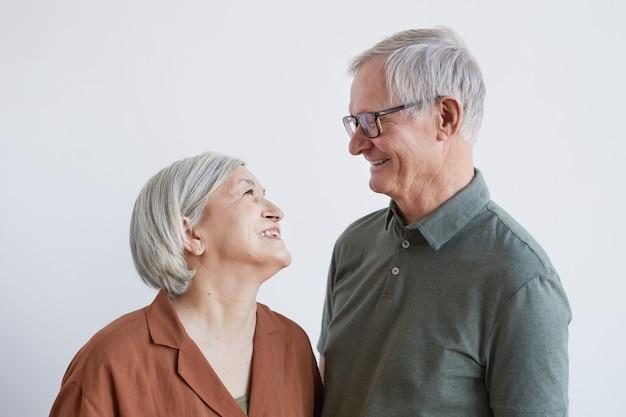 Portret van een gelukkig senior koppel dat elkaar liefdevol aankijkt terwijl ze tegen een witte achtergrond staan