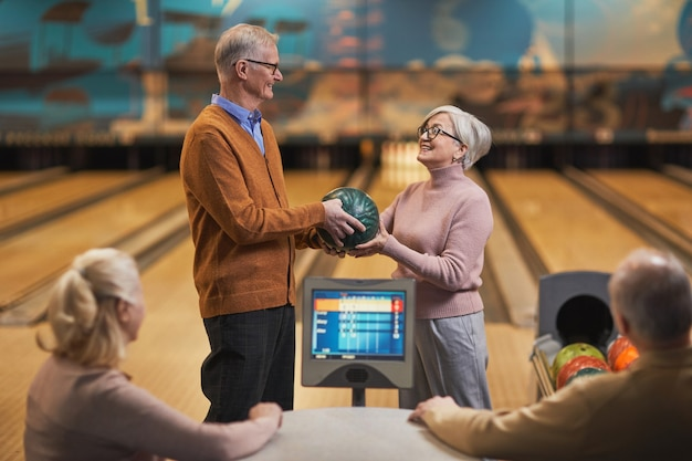 Portret van een gelukkig senior koppel dat samen met een groep vrienden bowlt in het entertainmentcentrum, kopieer ruimte