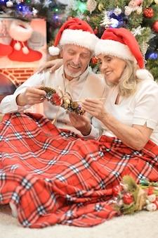 Portret van een gelukkig senior koppel in kerstmutsen die zich voorbereiden op kerstmis of nieuwjaar
