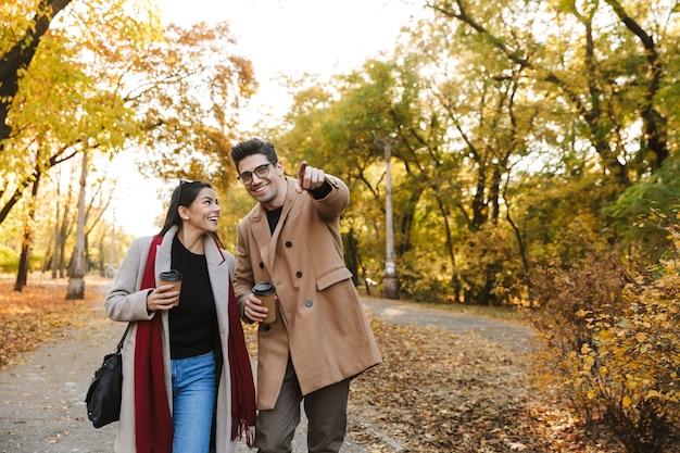 Portret van een gelukkig stel man en vrouw van 20 jaar die afhaalkoffie drinken uit papieren bekers tijdens het wandelen in het herfstpark