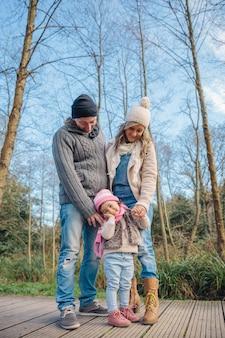Portret van een gelukkig stel met haar dochtertje dat samen geniet van vrije tijd over een houten pad naar het bos. familie tijd concept.
