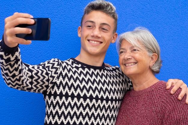 Portret van een gelukkig stel oma en kleinzoon in de tienerleeftijd die elkaar glimlachen en knuffelen terwijl ze naar de mobiele telefoon kijken voor een selfie. blauwe muur achtergrond