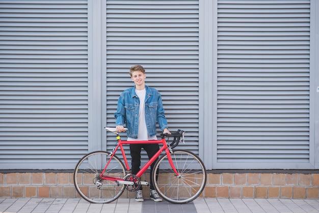 Portret van een gelukkig, stijlvolle jonge man in een spijkerjasje en een rode fiets op een grijze muur