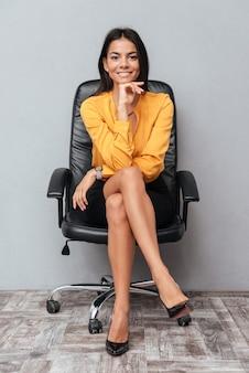 Portret van een gelukkig succesvol zakenvrouw zitten in de stoel