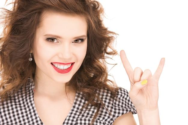 Portret van een gelukkig tienermeisje dat het gebaar van duivelshoorns toont