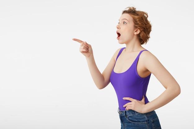 Portret van een gelukkig verbaasd jong aantrekkelijk korthaar meisje, gekleed in een paarse trui, zag iets ongelooflijk interessants en wijst met de vinger, kijk naar geïsoleerde kopie ruimte.