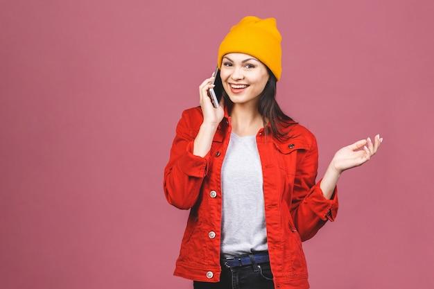 Portret van een gelukkig verbaasd vrouw in lichte kleding praten aan de telefoon geïsoleerd over roze muur.